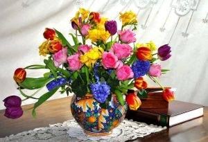 image shows a floral arrangement of tulips, daffodils and hyacinths in a vase